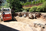 A machine moves boulders around in a yard