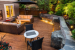 A cozy backyard retreat with a stone wall, two couches, and a fire pit