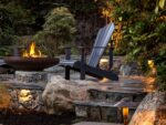 stone stairs lead to a raise patio, where two chairs sit by a fire pit