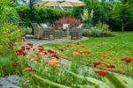 A table and chairs sit under a parasol in a lush garden