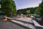Wide stone steps lead to a patio with a table and chairs