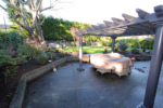 Before shot: a backyard area with an overhang and covered tables and chairs