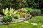 A stone path leads through a garden area